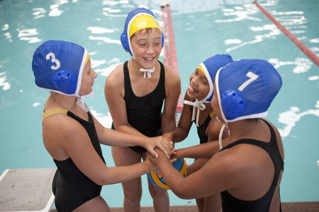 numeric: Four schoolgirl water polo players holding hands poolside LANG_EVOIMAGES