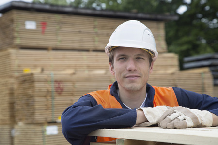 protective suit: Portrait of young male worker in timber yard