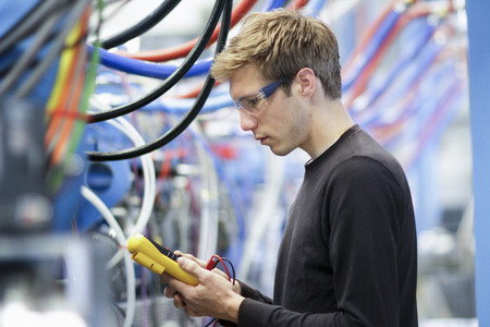 Mid adult male technician testing cables in engineering plant LANG_EVOIMAGES
