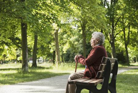 Senior woman sitting on park bench LANG_EVOIMAGES