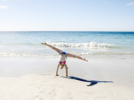 Girl doing handstand and splits on beach LANG_EVOIMAGES