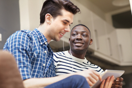 Two young men listening to music on digital tablet on living room sofa LANG_EVOIMAGES