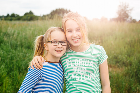Portrait of eleven year old girl hugging sister in field