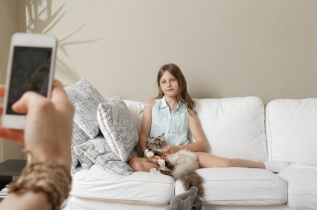 7 8: Mother photographing daughter with cat on sofa