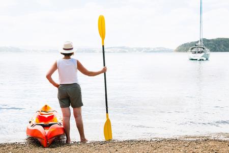 Rear view of senior woman and sea kayak