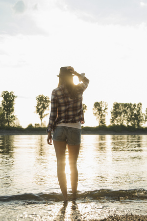 Young woman standing by lake LANG_EVOIMAGES