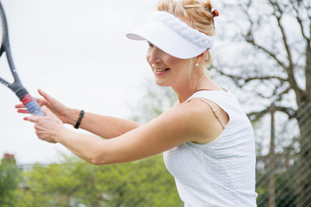 sun energy: Mature female tennis player playing tennis LANG_EVOIMAGES