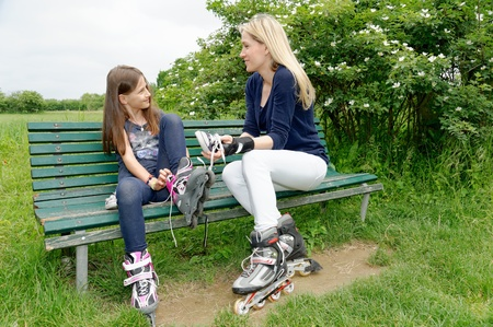 Mother and daughter putting on rollerblades in park