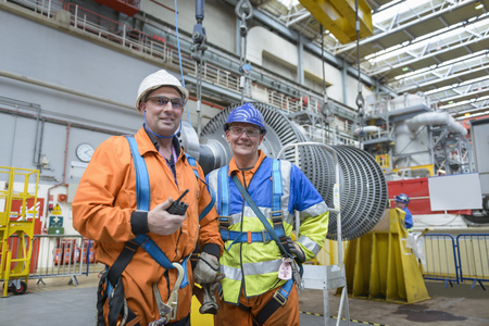 boiler suit: Banksman and crane operator in turbine hall during power station outage, portrait LANG_EVOIMAGES