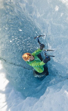 Mature female ice climber climbing out of pothole in glacier, Svinafellsjokull, Vatnajokull National Park, Iceland LANG_EVOIMAGES