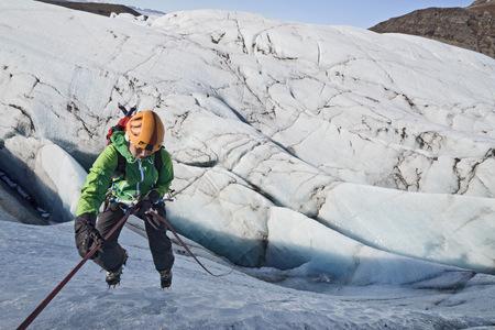 Female climber rappelling down glacier wall, Svinafellsjokull, Vatnajokull National Park, Iceland