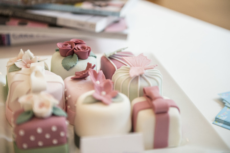 Close up of variety of individual decorated cakes in bakery