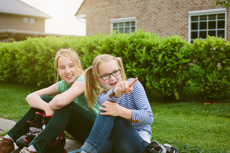 Two sisters sitting and pointing from sidewalk
