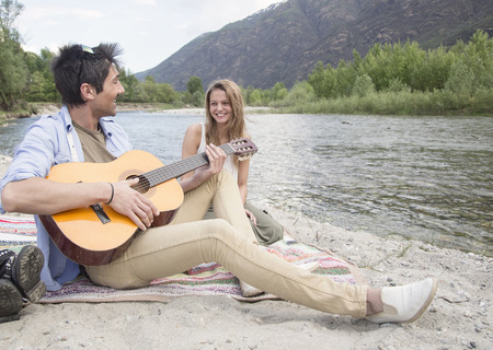 Friends sitting beside river, playing guitar