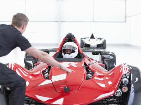 drivers seat: Engineer and racing car driver in supercar in sports car factory