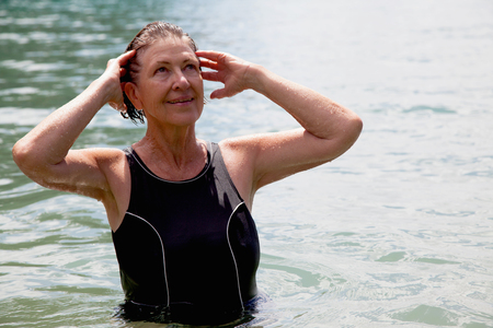 65 69 years: Senior woman swimmer with hands in wet hair