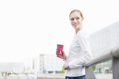 Young woman on city street with takeaway coffee