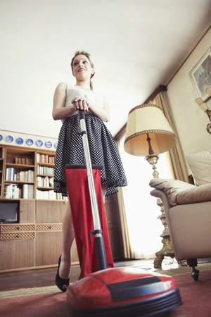 Low angle view of young woman in vintage clothes with vintage vacuum cleaner