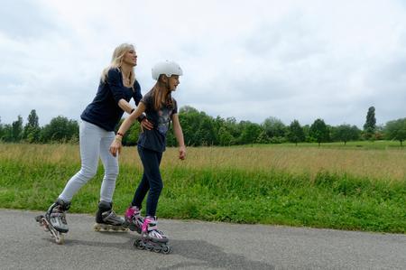 Madre sosteniendo hija mientras patina sobre ruedas en el parque