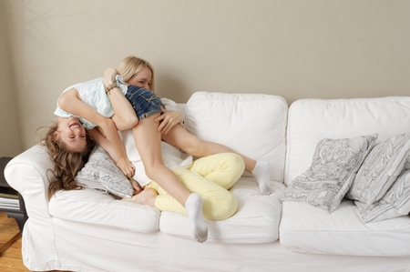 Mother and daughter playing on sofa