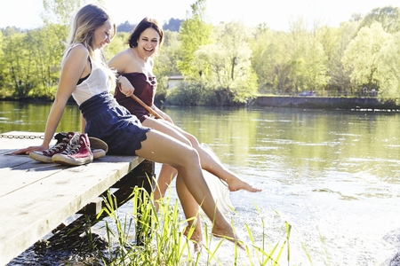 Young women sitting on jetty LANG_EVOIMAGES