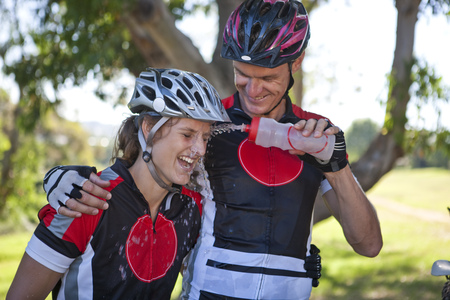 water quality: Male cyclist squirting water at womans face