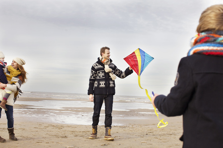 7 8: Mid adult parents with son and daughter playing with kite on beach, Bloemendaal aan Zee, Netherlands