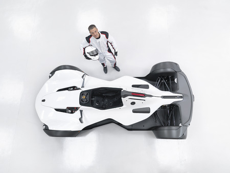 Portrait of racing driver next to supercar, overhead view