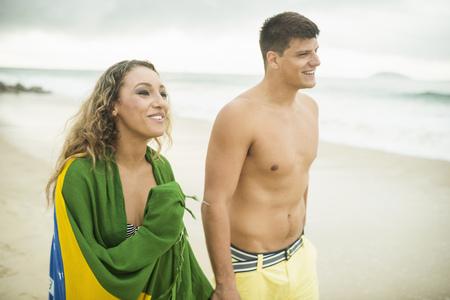 brazilian ethnicity: Young couple strolling on beach, woman wrapped in brazilian flag, Ipanema Beach, Rio de Janeiro, Brazil