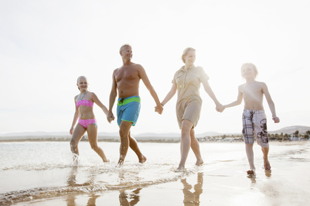 Family with two children strolling and holding hands on beach