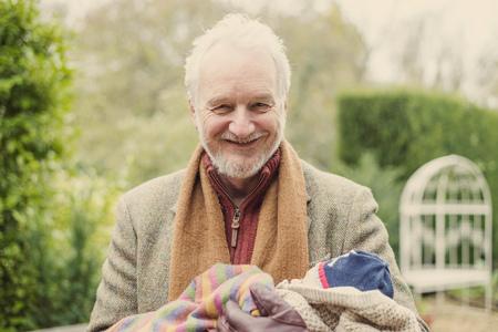 Grandfather cradling grandson, portrait LANG_EVOIMAGES