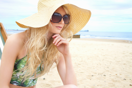 Portrait of young woman in sunhat and sunglasses at beach