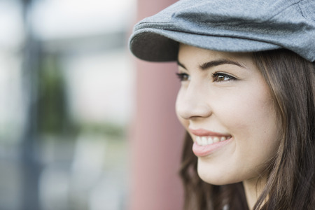 Young woman wearing flat cap, close up