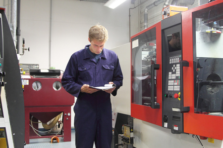 boiler suit: Male engineer checking machinery paperwork in factory LANG_EVOIMAGES