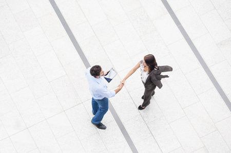 Dos personas dándose la mano en el concurso, alto ángulo