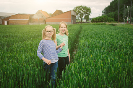Portrait of nine year old girl and sister on field path