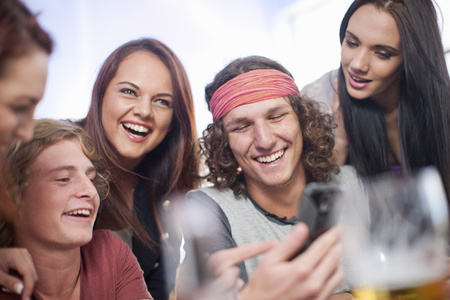 Group of five young adult friends looking at smartphone