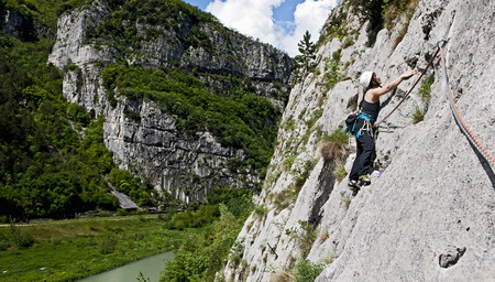 Woman climber traversing on multi pitch route, Amazziona at Piccolo Dain Parete della Centrale, Sarche, Trentino, Italy