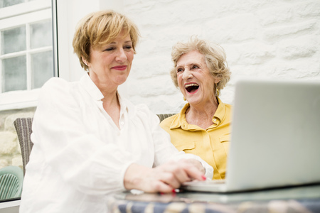 silver surfer: Senior woman and daughter, using laptop LANG_EVOIMAGES
