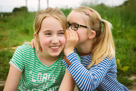 Nine year old girl whispering to sister in field