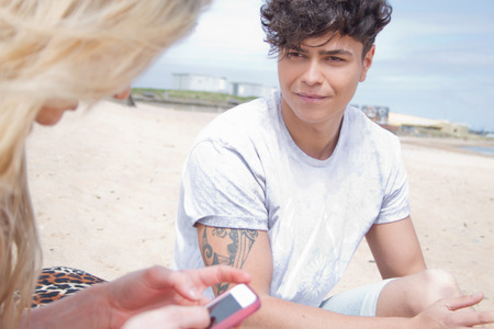 Young couple on beach with smartphone