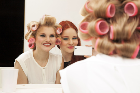 Young woman in curlers and friend taking selfie LANG_EVOIMAGES