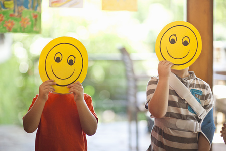 3 4 years: Two boys holding up smiley face masks at nursery school