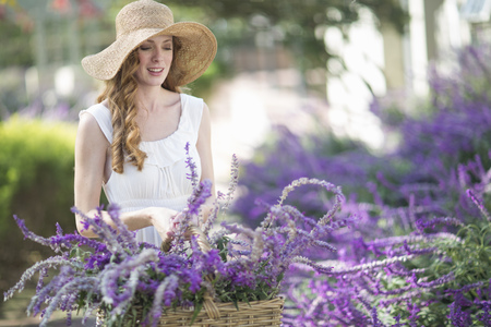 Beautiful young woman in garden looking at purple flowers