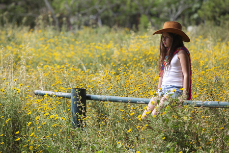 Sullen girl in cowboy hat sitting on fence in field LANG_EVOIMAGES