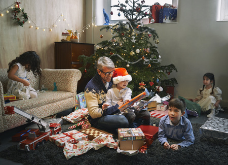 7 8: Father and four children opening christmas gifts in sitting room LANG_EVOIMAGES