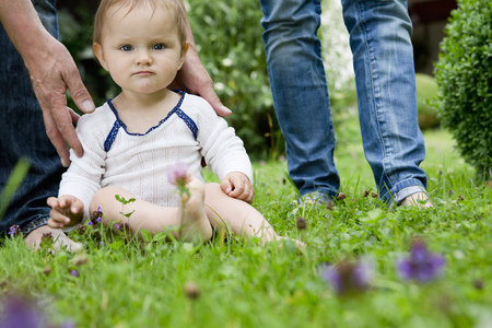 Portrait of baby girl sitting on lawn staring LANG_EVOIMAGES
