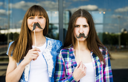 Portrait of two young women holding up mustache costume masks