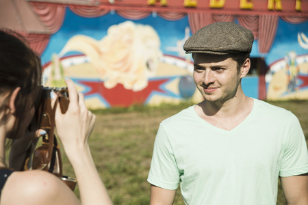 Young couple photographing on SLR camera at funfair