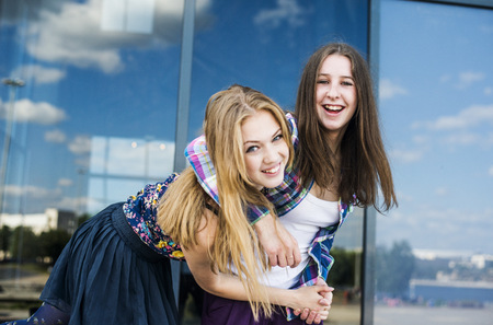 Portrait of two young women with arms around each other in city LANG_EVOIMAGES